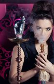 Beautiful woman smoking hookah in nightclub