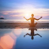 Yoga on the beach, relaxation, abstract photo about healthy lifestyle.
