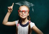 Genius girl in red glasses near blackboard in master hat