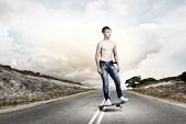 Young skater in jeans riding on road