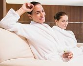 Portrait of two smiling young women in bathrobes drinking water