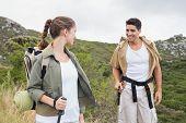 Portrait of hiking young couple walking on mountain terrain