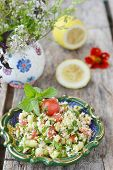 picture of tabouleh  - vegetables salad in to ornamental plate on wooden table  - JPG