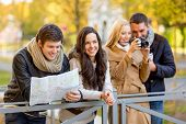 travel, vacation, technology, tourism and friendship concept - group of smiling friends with digital