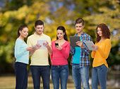 friendship, technology and people concept - group of smiling teenagers with smartphones and tablet p
