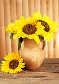 Beautiful bouquet of sunflowers in pitcher on table on wooden background