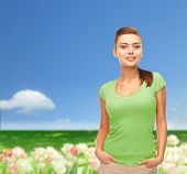t-shirt design and people concept - smiling young woman in blank green t-shirt