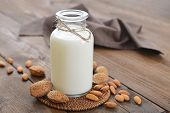 stock photo of milk  - Almond milk in bottle with nuts on wooden background
