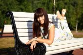 Cute young brunette woman in park sitting on the bench in summer park