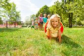 Blond girl and her friends play in tube on lawn