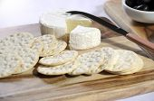 stock photo of penicillium  - Close of up of cheese platter with camembert cheese and water crackers on wooden boards and white tablecloth - JPG
