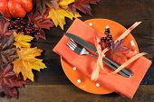 image of monarch  - Autumn Fall background with red brown and yellow leaves orange pumpkin and monarch butterfly on dark recycled rustic wood table with orange table place setting - JPG
