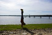 Man Handstands On Rocky Grassy Beach With Pier