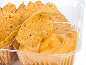 nachos chips with cheese sauce in plastic container  close up on white background