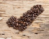 Checkmark From Coffee Beans On Wood Background