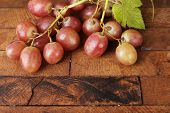 Pink grape on wooden table on wooden background