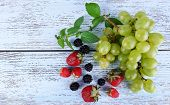 Different berries and grape on wooden table close-up
