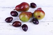 Beautiful ripe pears and plums on wooden table close-up