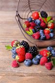 Ripe sweet different berries in metal basket, on old wooden table