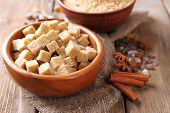 Brown sugar cubes, reed and crystal sugar in bowl with spices on wooden background