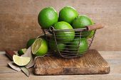 Fresh juicy limes in basket on old wooden background