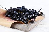 Purple grape on tray on wooden background