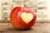 Red apple with heart on wooden table, close-up