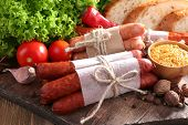 Assortment of thin sausages, bread, mustard in bowl and spices on cutting board, on wooden backgroun