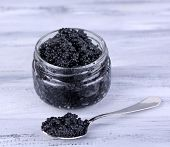 Glass jar and spoon of black caviar on grey wooden background