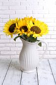 Beautiful bouquet of sunflowers in pitcher on table on brick wall background