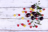 Beautiful ripe plums and berries on wooden table close-up