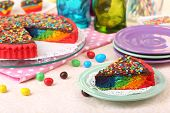 Delicious rainbow cake on table, on bright background