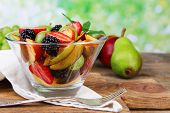 fresh tasty fruit salad on wooden table, on nature background