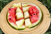 Watermelon and melon on bamboo plate on grass background