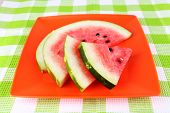 Watermelon on orange plate on  green tablecloth