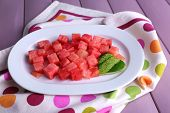 Slices of watermelon on polka dot napkin on wooden background