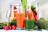 Jar of cut vegetables and glass of fresh vegetable juice with vegetables on wooden table