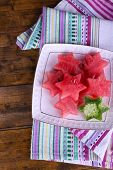 Pieces of melon and watermelon in plate on napkin on wooden background