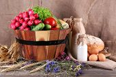 Big round wooden basket with vegetables, milk and bread on sacking background