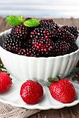 Bowl of blackberries and plate of strawberries on wooden table on light background