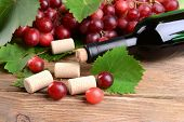 Wine bottle corks with grapes on table close-up