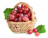 Sweet red grapes in wicker basket isolated on white