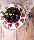 Bowl of blackberries and plate of strawberries on wooden background