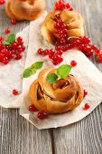 Tasty buns with berries on table close-up