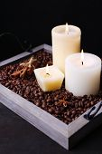 Candles on vintage tray with coffee grains and spices on wooden table, on dark background