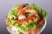 Fresh boiled prawns with lettuce in a goblet on grey background