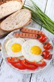 Scrambled eggs with sausage and vegetables served on plate on wooden background