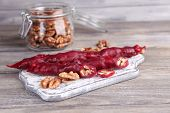 Tasty oriental sweets (churchkhela) and fresh nuts in glass jar, on wooden background