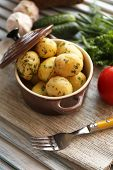Young boiled potatoes in pan on wooden table