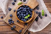 Wooden bowl of blueberries on cutting board on sacking napkin on wooden background
